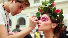 Man do makeup for model with flowers and leaves hair adornment - stock footage