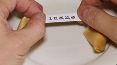 Opening a fortune cookie with numbers Stock Footage