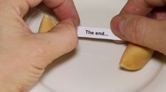 Opening a fortune cookie with: The end - stock footage