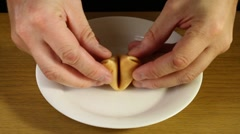 Opening a fortune cookie - stock footage