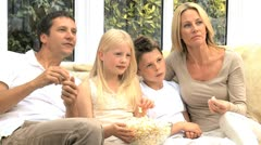 Attractive Family Enjoying TV & Popcorn - stock footage