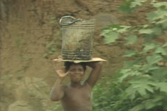 Boy carrying bucket on head Stock Footage