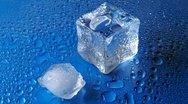 Melting ice on blue background Stock Footage