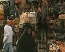 Local woman walking down market street with basket on head Stock Footage