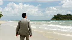 Stock Video Footage a man wearing a jacket on a beautiful beach  Stock Footage
