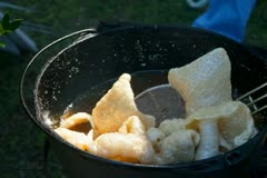 Stock Video Footage of Cooking large pork rinds in a large pot at the fair