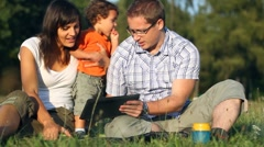 Happy family with tablet computer in the park, dolly shot HD Stock Footage