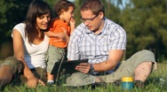 Stock Video Footage of Happy family with tablet computer in the park, dolly shot HD