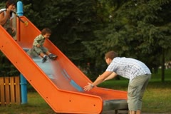 Young parents with their son on slide in the park NTSC Stock Footage
