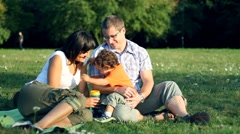 Stock Video Footage of Young parents with their son sitting in the park HD