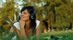 Woman with headphones lying on the grass HD Stock Footage