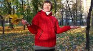 Speaking middle-aged woman in autumn park with maple leaves Stock Footage