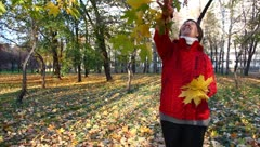 Middle-aged woman in a park, rips the leaves in autumn park - stock footage