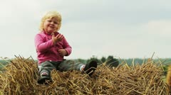 Child is sitting on a haystack Stock Footage
