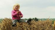 Stock Video Footage of child is sitting on a haystack