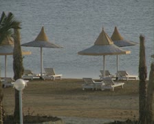 Zoom out from sun loungers on beach to empty resort bar Stock Footage