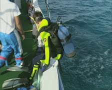 Scuba diver rolling off boat into sea Stock Footage
