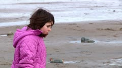 Slow motion of cute, little girl walking on beach in winter Stock Footage