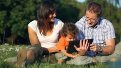 Happy family with tablet computer in the park - stock footage