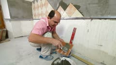 Man installs ceramic tile Stock Footage