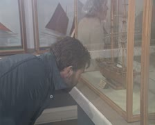 Man looking at model ship in display case Stock Footage