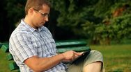 Stock Video Footage of Young happy man with tablet computer sitting in the park