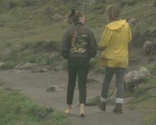 Two people walking along coastal path Stock Footage