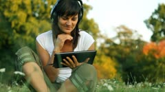 Young woman with tablet computer and headphones on meadow - stock footage