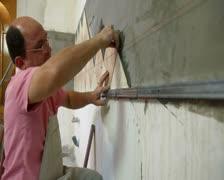 Man applying ceramic tile to  Kitchen wall Stock Footage