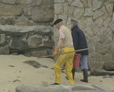 People walking along beach carrying fisherman baskets Stock Footage