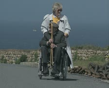 Woman wheeling man in wheelchair into restaurant Stock Footage