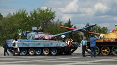 Kids playing around two old colored military tanks NO WAR Stock Footage