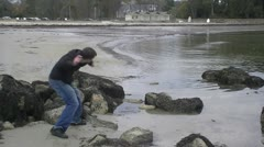 Young man skipping rocks Stock Footage