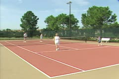 Family playing tennis on court Stock Footage