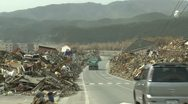 Stock Video Footage of Japan Tsunami Aftermath - Debris Pilled Along Side Of Road