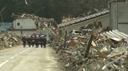 Japan Tsunami Aftermath - Rescuers Walk Through Destroyed Streets Stock Footage