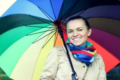 Woman walking with colorful umbrella Stock Footage