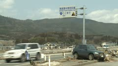 Japan Tsunami Aftermath - Wrecked Car Near Tsunami Warning Sign On Highway - stock footage
