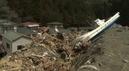 Japan Tsunami Aftermath - Boat Lies On Railway Embankment In Destroyed Town Stock Footage