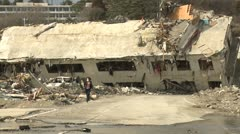Japan Tsunami Aftermath - Woman Runs From Destroyed Building In Onagawa City Stock Footage