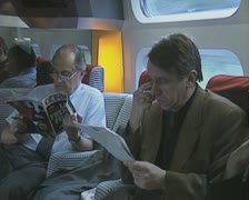 Men sitting in moving train and reading Stock Footage