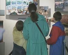 Family looking at Disneyland museum display Stock Footage