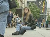 Stock Video Footage of Young woman sitting in street