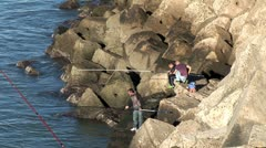 WorldClips-Cadiz Fishermen on Rocks Stock Footage