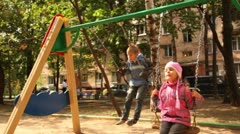 Boy and little girl sway on swing at playground Stock Footage