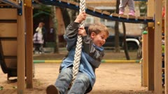 Boy sway on rope at playground Stock Footage