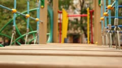 Little girl run on hang down wooden steps few times at playground Stock Footage