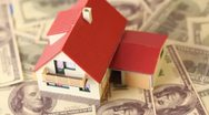 Toy house with red tiled roof on dollars bank notes Stock Footage
