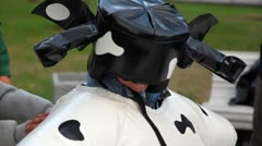 Boy in cow suit and helm smile, people stand around Stock Footage