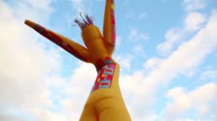 Colorful inflated man dance at background of sky with clouds Stock Footage
